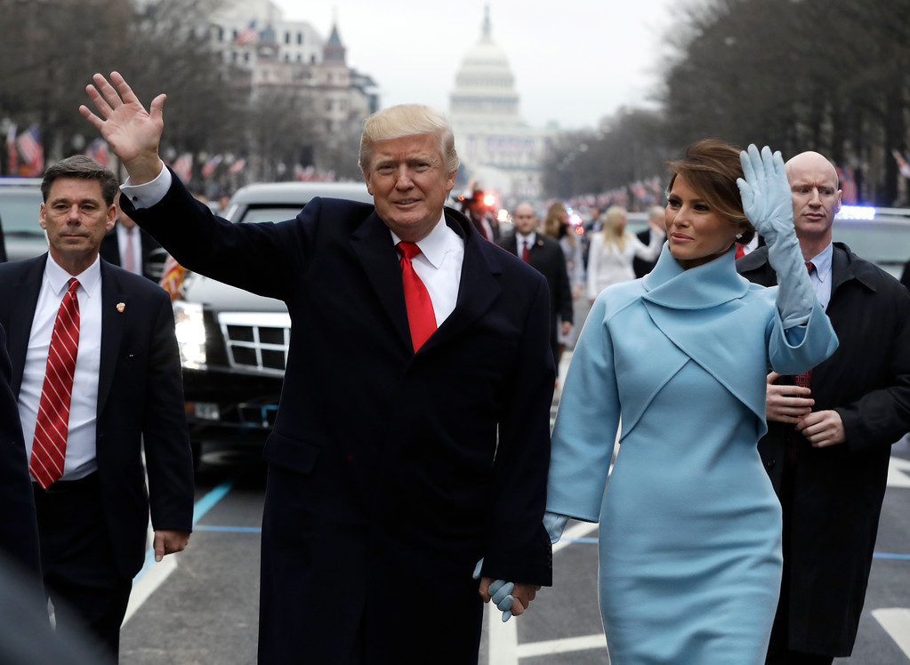 . President Donald Trump waves as he walks with first lady Melania Trump during the inauguration parade on Pennsylvania Avenue in Washington, Friday, Jan. 20, 2016. (AP Photo/Evan Vucci, Pool)