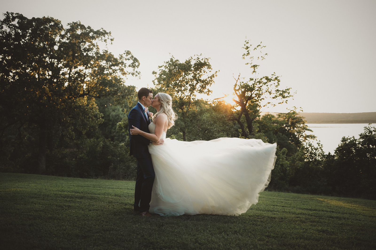 bride and groom kissing at sun down after their wedding with a gorgeous lakeside view