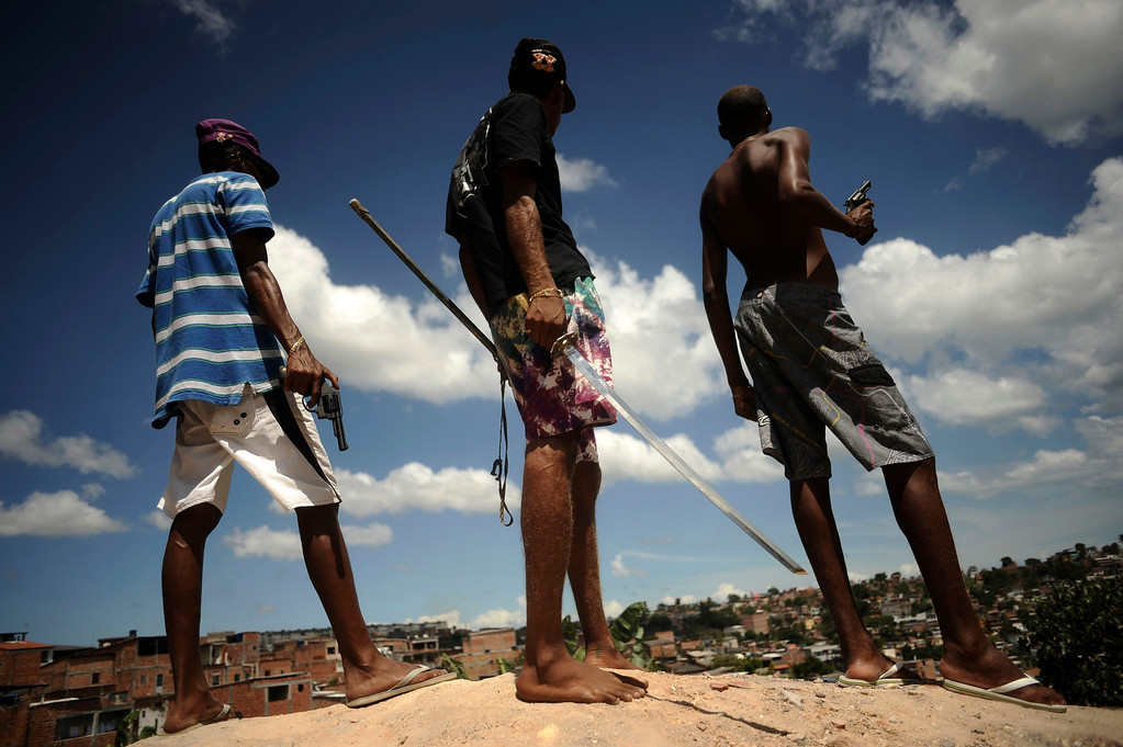 . Brazilian drug gang members pose with weapons atop a hill overlooking a slum in Salvador, Bahia State, April 11, 2013. One of Brazil\'s main tourist destinations and a 2014 World Cup host city, Salvador suffers from an unprecedented wave of violence with an increase of over 250% in the murder rate, according to the Brazilian Center for Latin American Studies (CEBELA). Picture taken April 11, 2013.  REUTERS/Lunae Parracho