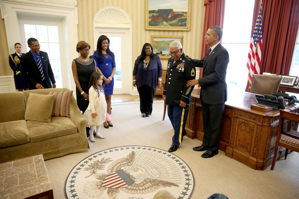 . U.S. President Barack Obama stands with U.S. Army Staff Sgt. (Ret.) Melvin Morris, a Vietnam War veteran, as his family looks on in the Oval office before a ceremony presenting him with the Medal of Honor at the White House on March 18, 2014 in Washington,DC. Melvin Morris and two others are the only living soldiers who were honored with 21 others today at the White House by President Barack Obama with the Medal of Honor.  (Photo by Joe Raedle/Getty Images)