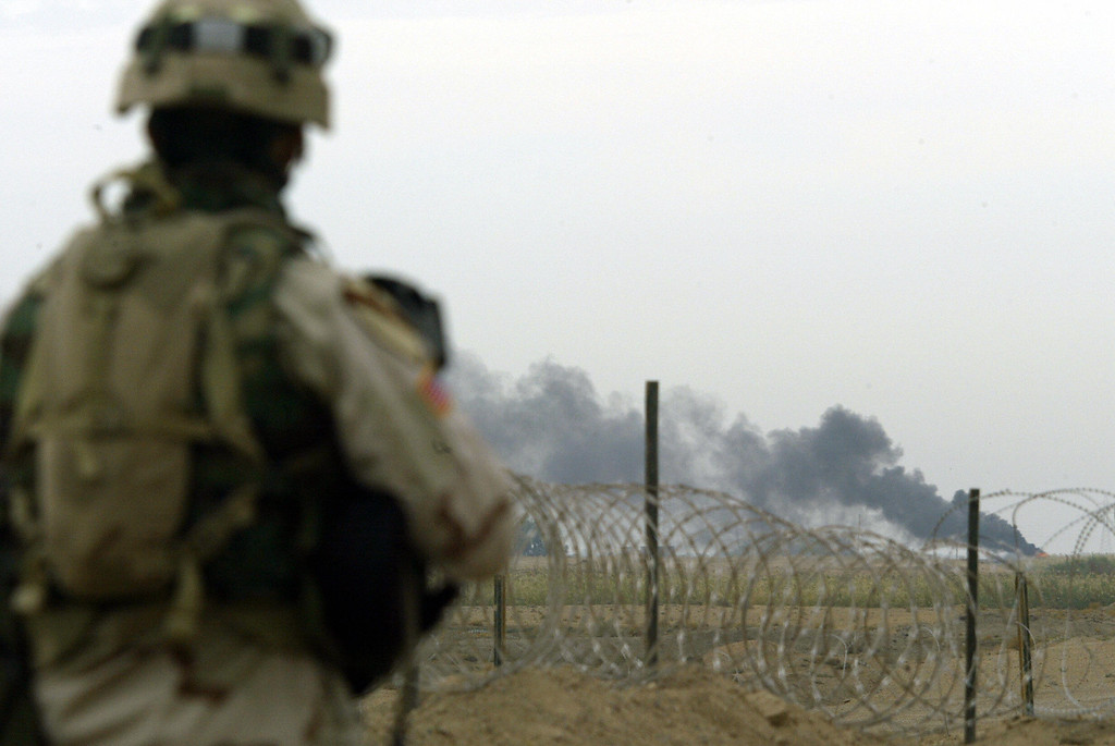 . A US soldier with 1/5 Cavalery looks at a plume of smoke billowing from the northern entrance of Fallujah, 50 kms west of Baghdad 08 November 2004.  AFP PHOTO/PATRICK BAZ/AFP/Getty Images)