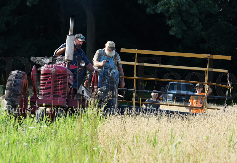 Harold Aughton/Butler Eagle: Terry Foertsch (left), his dad, Vernon and children, Timothy, 11, and Granite, 15, of Saxonburg recently cut about 1 1/2 acres of oats with an old-fashion grain binder on Guy Daubenspeck's farm in Connoquennessing Twp. The Foertsch family and others will be separating the straw and chaff from the grain using a threshing machine at this year's farm show.