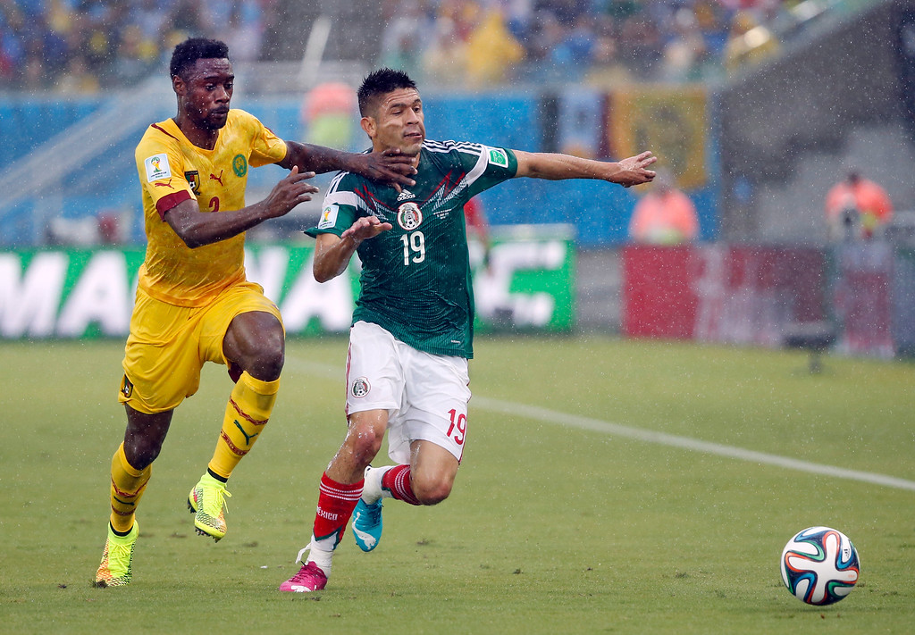 . Cameroon\'s Benoit Assou-Ekotto, left, and Mexico\'s Oribe Peralta fight for the ball during the group A World Cup soccer match between Mexico and Cameroon in the Arena das Dunas in Natal, Brazil, Friday, June 13, 2014.  (AP Photo/Sergei Grits)
