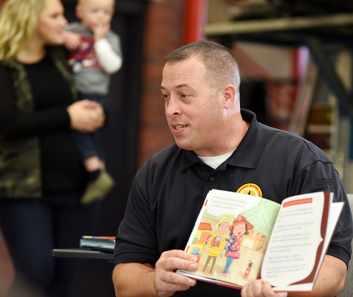 Harold Aughton/Butler Eagle: Adams Fire Chief Tim Llewellyn reads to about 60 children and their parents during the Mars Library's story time held at the fire station, Tues., Oct. 8.