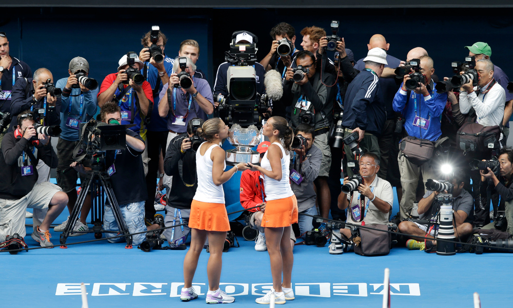 Description of . Italy's Sara Errani, left, and Roberta Vinci kiss their trophy for photographers after winning the women's doubles final against Australia's Ashleigh Barty and Casey Dellacqua at the Australian Open tennis championship in Melbourne, Australia, Friday, Jan. 25, 2013. (AP Photo/Andy Wong)