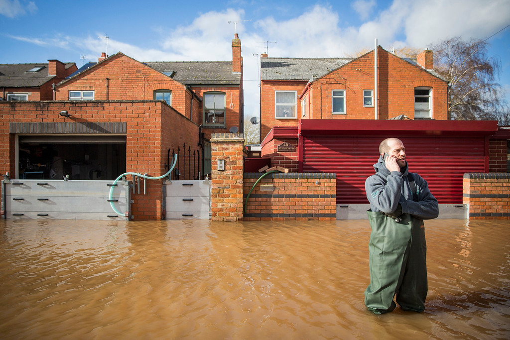 . A resident of Waterworks Road stands in floodwater on February 13, 2014 in Worcester, Worcestershire, England. The Environment Agency has issued flood warnings for dozens of areas along the River Severn. (Photo by Rob Stothard/Getty Images)