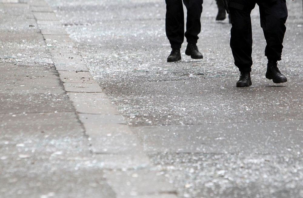 . Police officers walk over shattered glass after an explosion in Prague April 29, 2013. The explosion in central Prague on Monday injured about a dozen people and others were trapped in a building damaged by the blast, a Reuters witness and emergency services officials said.  REUTERS/David W Cerny