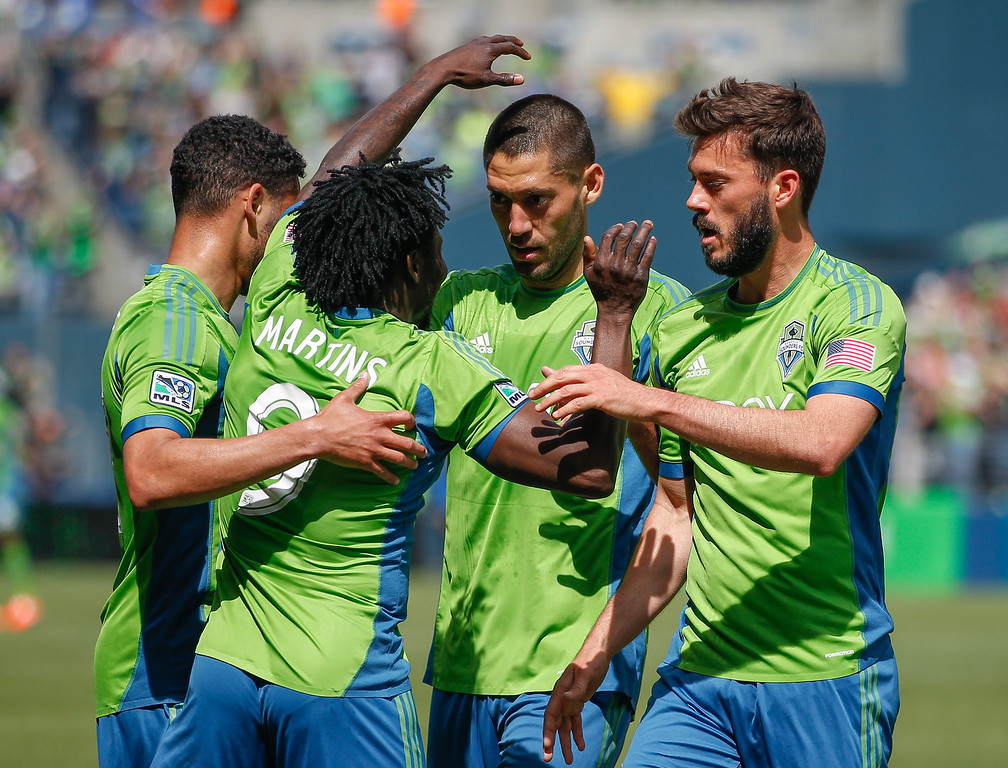 . Obafemi Martins #9 of the Seattle Sounders FC is congratulated by Lamar Neagle #27 (far left), Clint Dempsey #2, and Brad Evans #3 after scoring a goal in the second half against the Colorado Rapids at CenturyLink Field on April 26, 2014 in Seattle, Washington. The Sounders defeated the Rapids 4-1. (Photo by Otto Greule Jr/Getty Images)