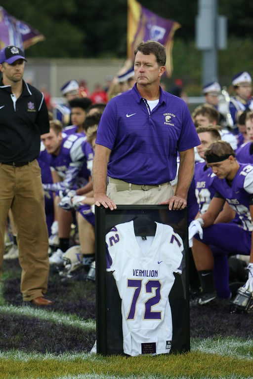 . Kyle Sooy - The Morning Journal<br> Vermilion coach Brett Colahan presents the family of late coach Matt Kobal with a jersey in his honor prior to the Sailors game against Firelands on Sept. 7.