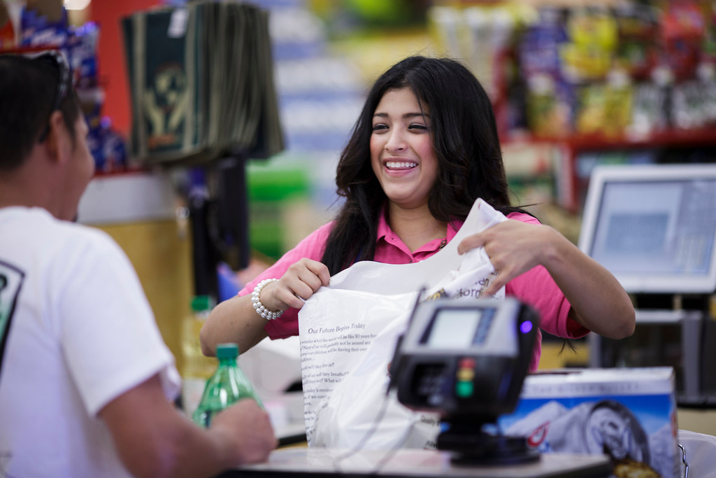 . Gabriela Urbina, a casher at Mi Pueblo Food Center smiles at her customer on July 24, 2013 in San Jose. The Bay Area supermarket chain filed for Chapter 11 bankruptcy protection Monday, citing a dispute with its primary lender, Wells Fargo. (Dai Sugano/Bay Area News Group)