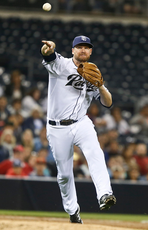 . San Diego Padres third baseman Chase Headley  makes the running throw to get Colorado Rockies\' DJ LeMahahieu at first in the second inning of a baseball game Monday, April 14, 2014, in San Diego. (AP Photo/Lenny Ignelzi)