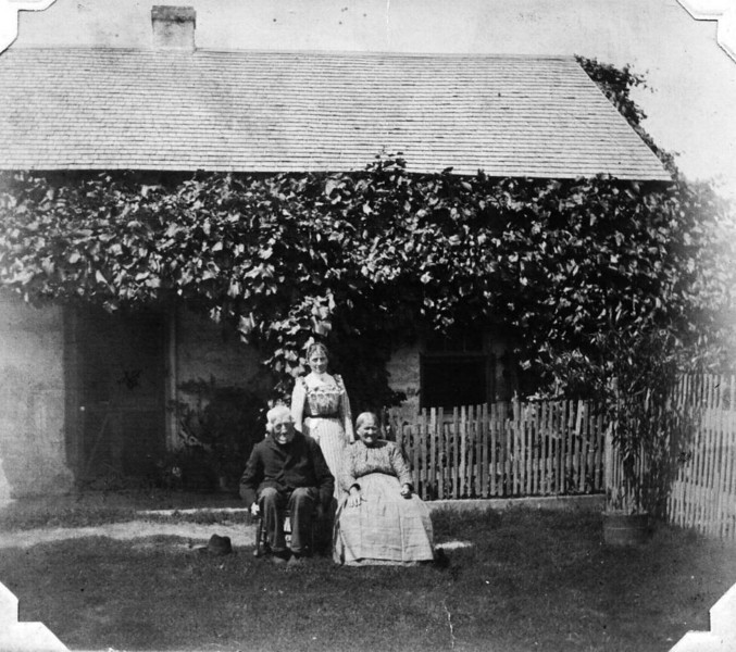 Carl Moritz, Wendelina & Molly Liebe in front of their ivy-covered log cabin at Mosel, Sheboygan County, Wisconsin.