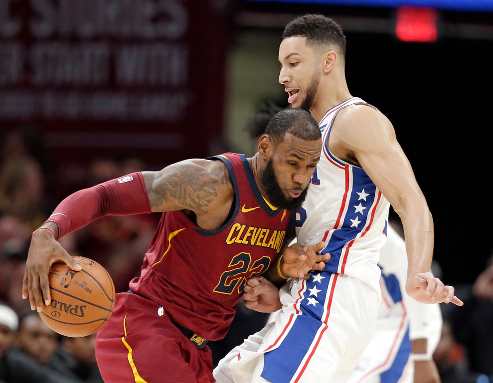 . Cleveland Cavaliers\' LeBron James, left, drives past Philadelphia 76ers\' Ben Simmons during the first half of an NBA basketball game, Saturday, Dec. 9, 2017, in Cleveland. (AP Photo/Tony Dejak)