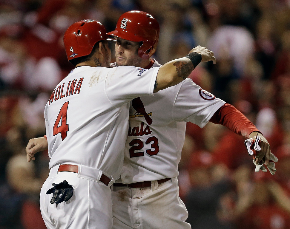 . St. Louis Cardinals\' David Freese and Yadier Molina celebrate after both scored on a hit by Shane Robinson during the third inning of Game 6 of the National League baseball championship series against the Los Angeles Dodgers Friday, Oct. 18, 2013, in St. Louis. (AP Photo/Jeff Roberson)