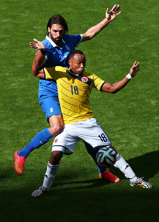 . Juan Camilo Zuniga of Colombia holds off a challenge by Giorgos Samaras of Greece during the 2014 FIFA World Cup Brazil Group C match between Colombia and Greece at Estadio Mineirao on June 14, 2014 in Belo Horizonte, Brazil.  (Photo by Ian Walton/Getty Images)