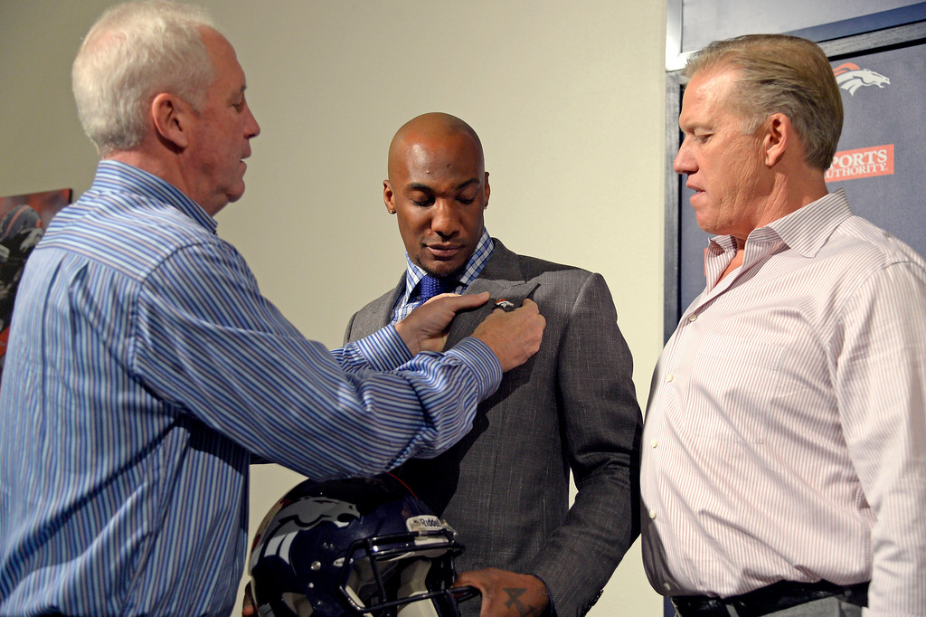 . Denver Broncos head coach John Fox fixes a Broncos lapel pin on Aqib Talib jacket as John Elway, General Manager and Executive Vice President of Football Operations looks on after a press conference March 12, 2014 at Dove Valley. (Photo by John Leyba/The Denver Post)