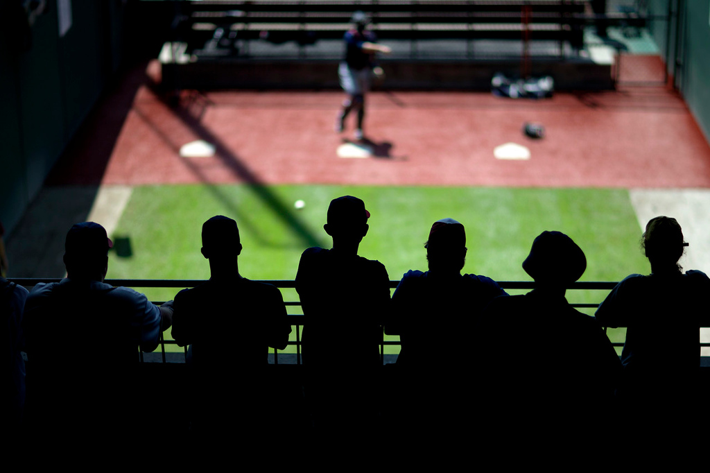 . Fans watch as Twins\' Ryan Doumit, top, warms up with pitcher Vance Worley, not pictured, in the bullpen before the start of their game against the Braves. (AP Photo/David Goldman)