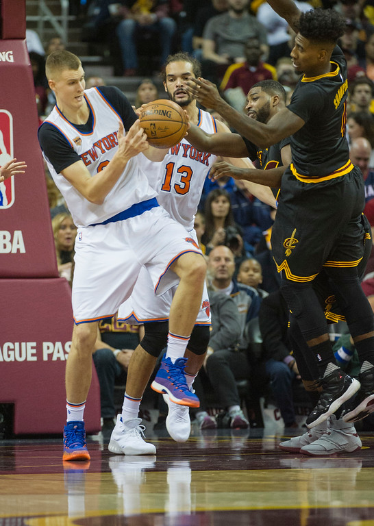 . New York Knicks\' Kristaps Porzingis (6) grabs a rebound from Cleveland Cavaliers\' Iman Shumpert as New York Knicks\' Joakim Noah (13) watches during the first half of an NBA basketball game in Cleveland, Tuesday, Oct. 25, 2016. (AP Photo/Phil Long)