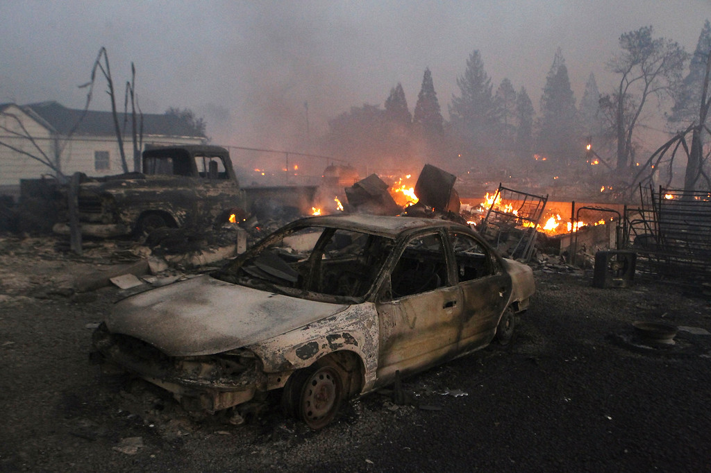 . In this Monday, Sept. 15, 2014 photo, vehicles and homes are destroyed in Weed, Calif. where a wind-driven wildfire raced through the hillside neighborhood and forced more than 1,000 people to flee the small town near the Oregon border. (AP Photo/The Record Searchlight, Greg Barnette)