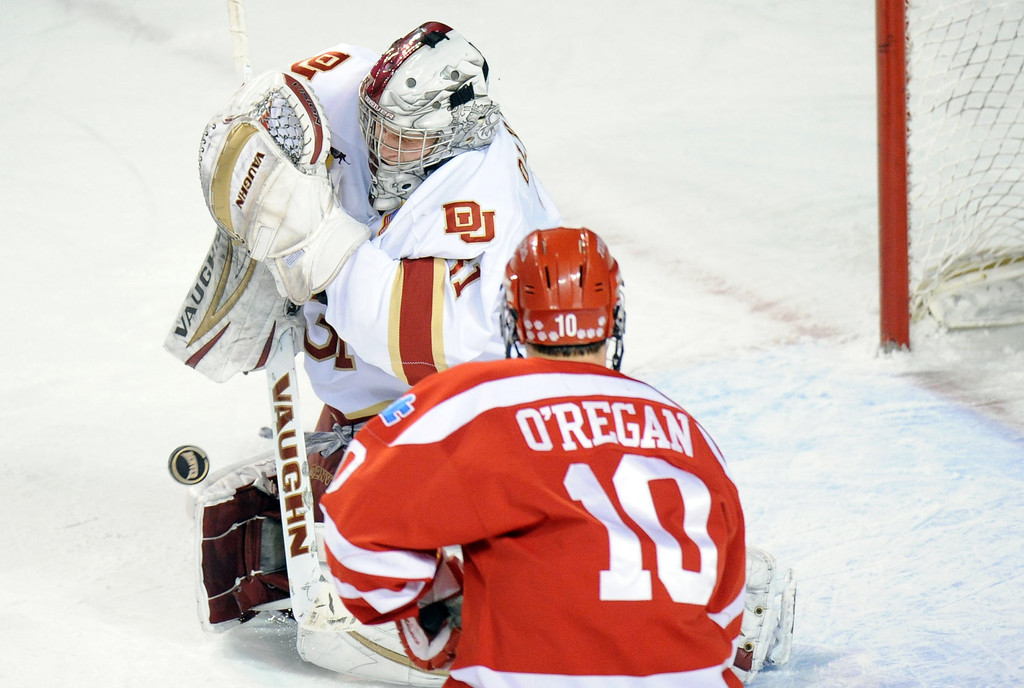 . University of Denver goalie Juho Olkinuora (31), left, blocks a shot by Boston University\'s  Danny O\'Regan (10) in the 1st period of the game at Magness Arena on in Denver on Saturday, Dec. 29, 2012. Hyoung Chang, The Denver Post