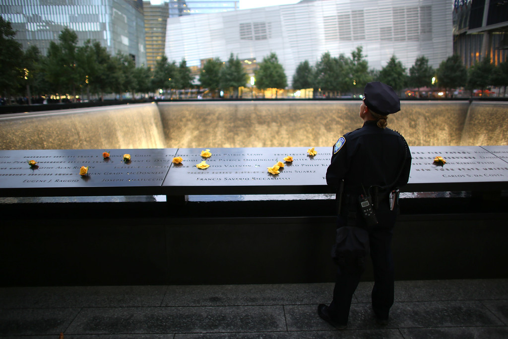 . Port Authority Police Officer Donna Przybyszewski reflects on the colleagues she knew who lost their lives during the attacks of Sept. 11, 2001, at the South Tower Memorial Pool before memorial observances held at the site of the World Trade Center in New York, Thursday, Sept. 11, 2014. (AP Photo/The New York Times, Chang W. Lee, Pool)