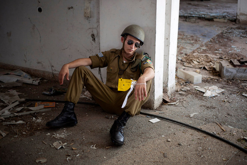 . An Israeli soldier acting as if he is wounded waits for Israeli soldiers of the Home Front Command rescue unit during a drill in Azur, near Tel Aviv, Israel, Tuesday, May 28, 2013. Israel has launched a national civil defense drill, which the army said this year will focus on the threat of unconventional weapons at a time of growing regional tensions. (AP Photo/Ariel Schalit)