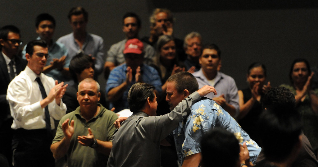. Former cross-country coach James O\'Brien, center, receives a standing ovation from over 200 people that crowded the Arcadia Unified School District Performing Arts Center as a show of support for fired Arcadia High School cross-country coach James O\'Brien during a Arcadia Unified School District Board of Education meeting on Tuesday, July 23, 2013 in Arcadia, Calif. O\'Brien, led the team to two time state and national championships.