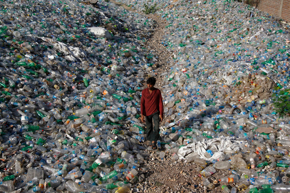 . A man walks between heaps of plastic bottles at an industrial area on World Environment Day on the outskirts of Jammu, India, Wednesday, June 5, 2013. World Environment Day is celebrated every year by the United Nations to stimulate global awareness on environmental issues.  (AP Photo/Channi Anand)