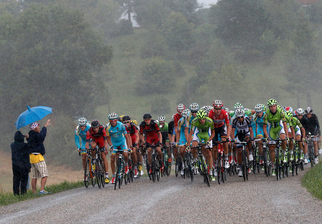 . The pack rides in the rain during the nineteenth stage of the Tour de France cycling race over 208.5 kilometers (129.6 miles) with start in Maubourguet and finish in Bergerac, France, Friday, July 25, 2014. (AP Photo/Christophe Ena)