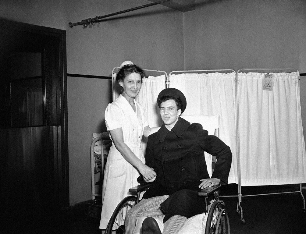 . U.S. Coast Guardsman Clifford Johnson, 22, of Sumner, Mo., won a year-long battle for survival after sustaining burns on 67% of his body in the Cocoanut Grove fire last November. He is at Boston City Hospital before discharge, Nov. 26, 1943 with Miss Mercy Smith, his nurse and constant winner in innumerable gin rummy games during his hospitalization. (AP Photo/Abe Fox)