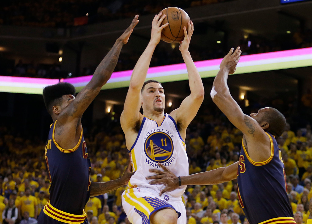 . Golden State Warriors guard Klay Thompson (11) shoots between Cleveland Cavaliers guard Iman Shumpert, left, and forward James Jones during the second half of Game 5 of basketball\'s NBA Finals in Oakland, Calif., Sunday, June 14, 2015. (AP Photo/Ben Margot)