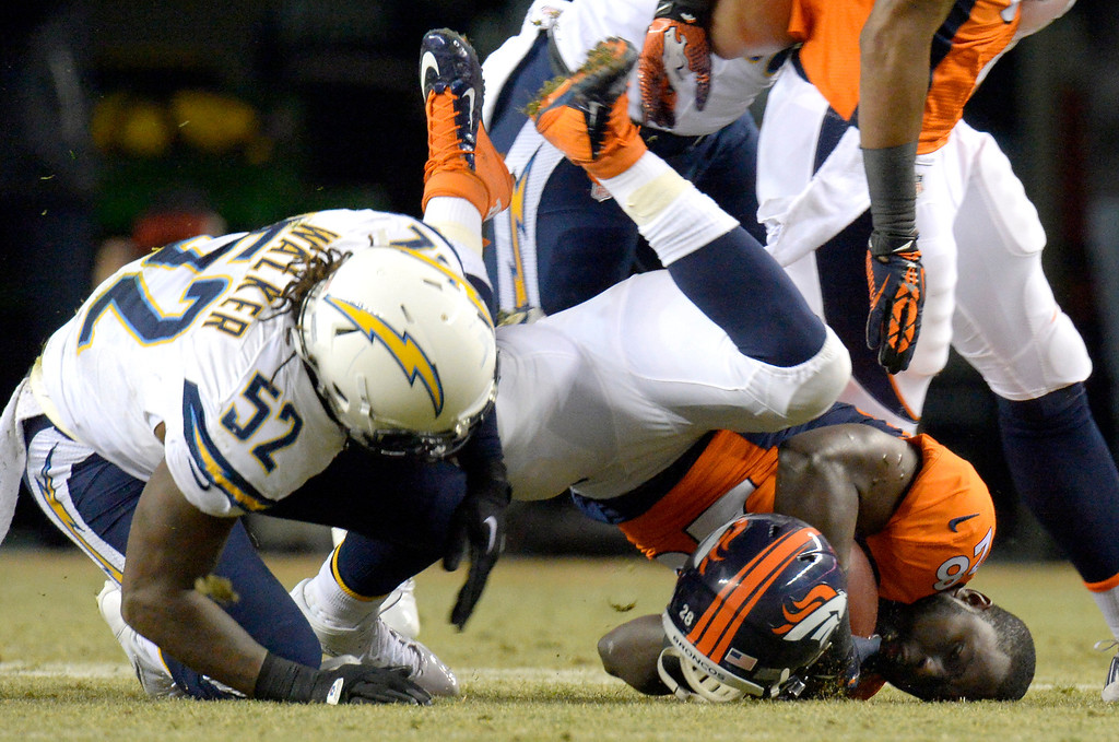 . Denver Broncos running back Montee Ball (28) hits the turf without his helmet after being tackled by San Diego Chargers inside linebacker Reggie Walker (52) during the first quarter. The Denver Broncos vs. the San Diego Chargers at Sports Authority Field at Mile High in Denver on December 12, 2013. (Photo by John Leyba/The Denver Post)