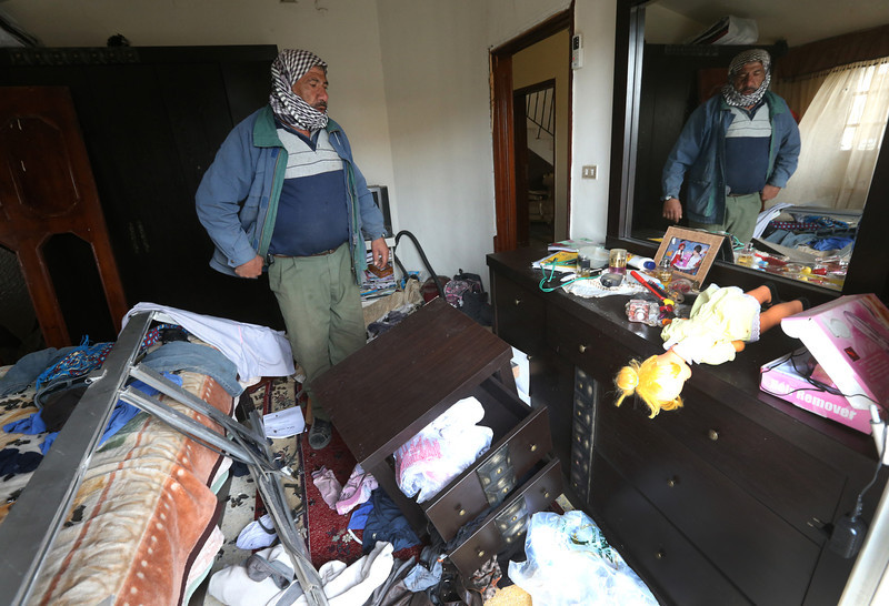 . A Lebanese man checks the damage inside his bedroom, near the site where a deadly car bomb exploded Saturday evening, in the predominately Shiite town of Hermel, about 10 miles (16 kilometers) from the Syrian border in northeast Lebanon, Sunday, Feb. 2, 2014. (AP Photo/Hussein Malla)