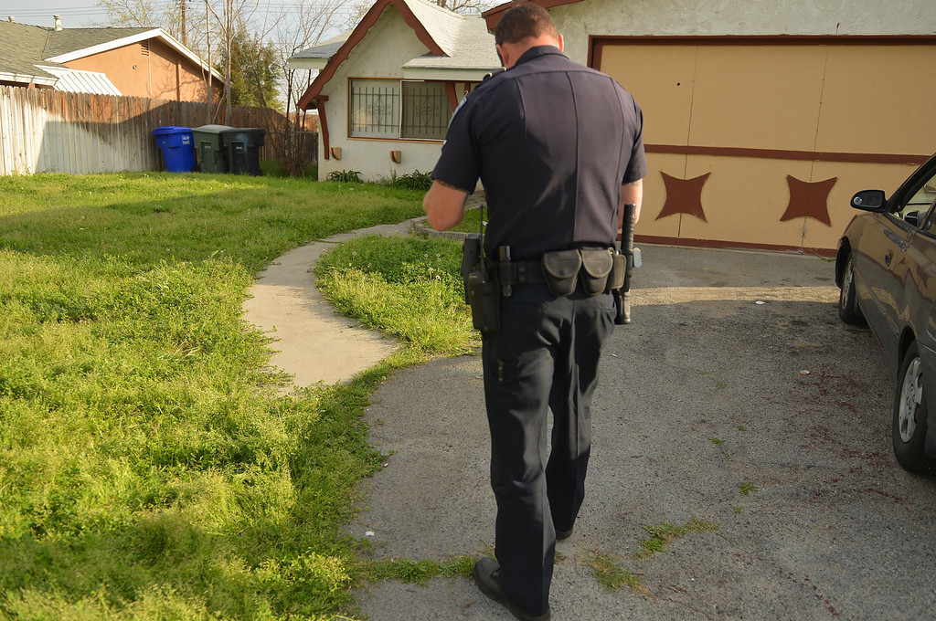 . San Bernardino Police Officer Chris Flowers, investigates the scene where a man was shot multiple times, Wednesday March 5, 2014, after pulling into his driveway in the 2000 block of West Gilbert Street, San Bernadino. (Photo by LaFonzo Carter/The Sun)
