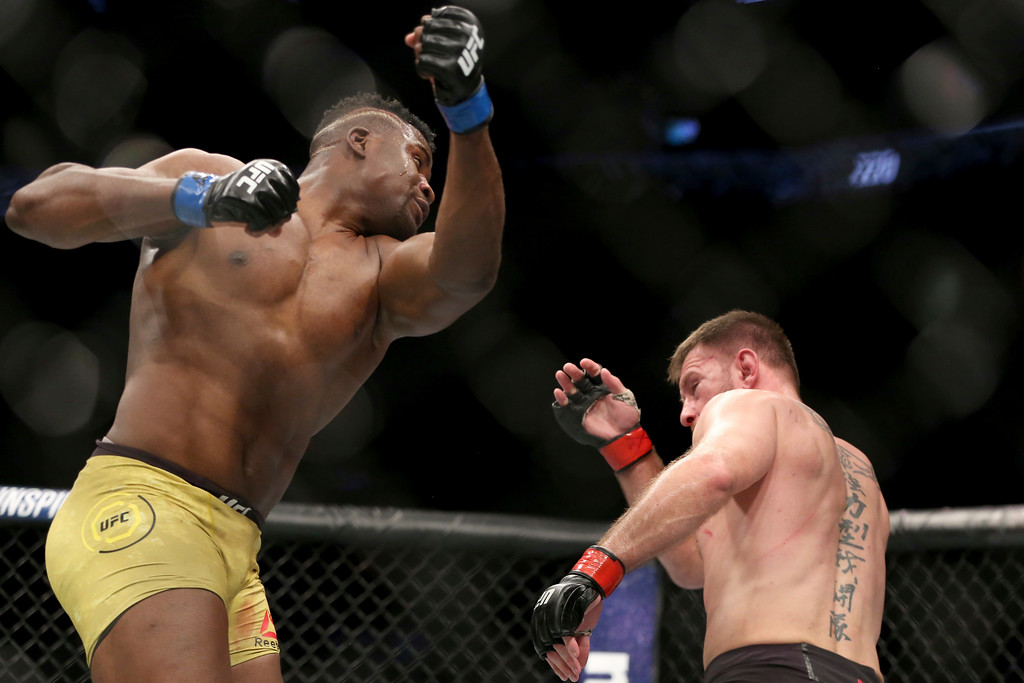 . Francis Ngannou misses with an uppercut against Stipe Miocic during a heavyweight championship mixed martial arts bout at UFC 220, early Sunday, Jan. 21, 2018, in Boston. Miocic retained his title via unanimous decision. (AP Photo/Gregory Payan)