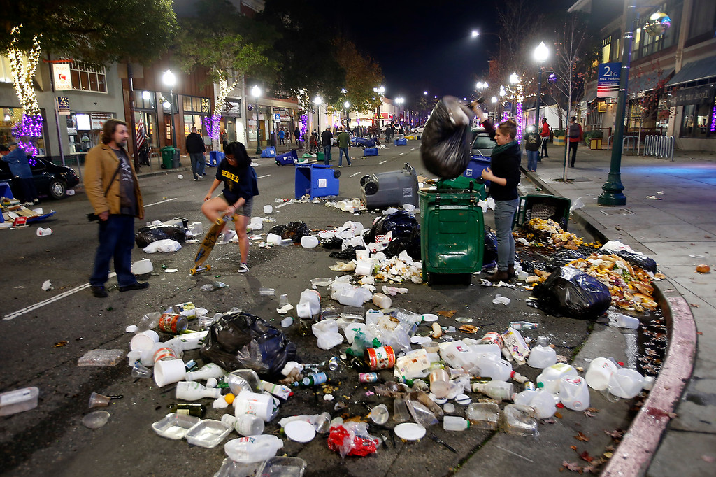 . Cal students clean up a mess left by protesters along Shattuck Avenue in Berkeley, Calif., late Sunday evening, Dec. 7, 2014, during a second consecutive night of unrest in the city over the killings of two unarmed black men by police in Ferguson, Mo., and New York. (Karl Mondon/Bay Area News Group)