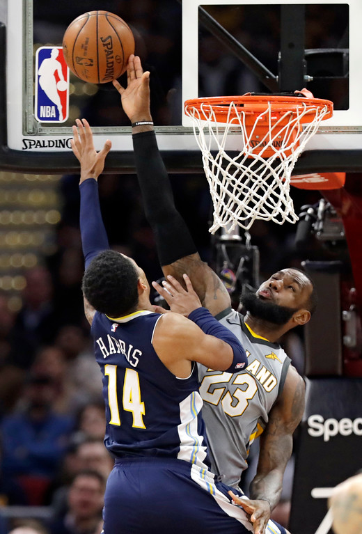 . Cleveland Cavaliers\' LeBron James, right, attempts to block a shot by Denver Nuggets\' Gary Harris in the first half of an NBA basketball game, Saturday, March 3, 2018, in Cleveland. James was called for a foul. (AP Photo/Tony Dejak)