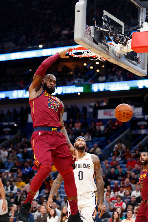 . Cleveland Cavaliers forward LeBron James (23) slam dunks in front of New Orleans Pelicans forward DeMarcus Cousins (0) in the first half of an NBA basketball game in New Orleans, Saturday, Oct. 28, 2017. (AP Photo/Gerald Herbert)