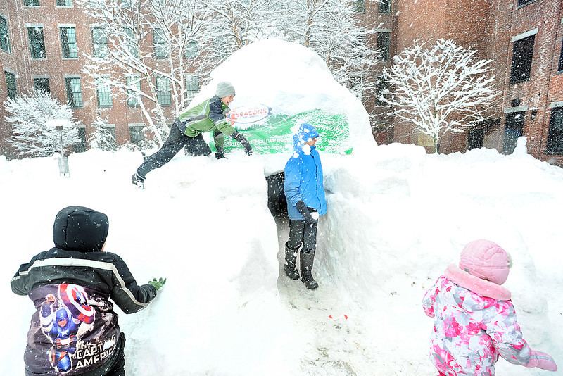 Ethan Brown, 12, of Auburn, blue coat, gets a snowball in the head from his brother Austin, 11, as he exits the igloo Sunday afternoon during the last day of the Ice Festival of Lewiston/Auburn at Fountain Park in Lewiston.