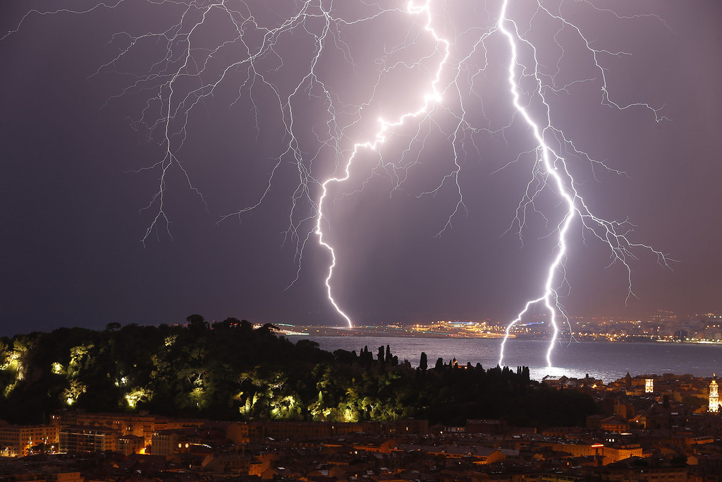 ". Flashes of lightning strike above the ""Baie des Anges\"", on October 4, 2013, in Nice, southeastern France. VALERY HACHE/AFP/Getty Images"