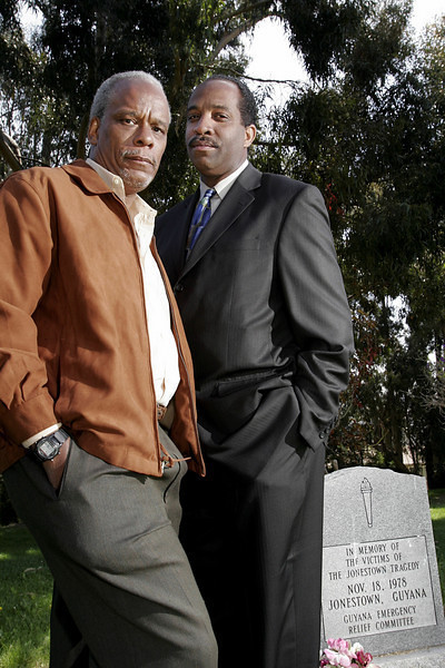 Filmmaker Stanley Nelson, left, who created a documentary on Jim Jones and the Jonestown tragedy, visited a memorial tombstone with the cult leader's adopted son Jim Jones Jr. at Evergreen Cemetery in Oakland, Calif. (AP Photo/Dino Vournas)