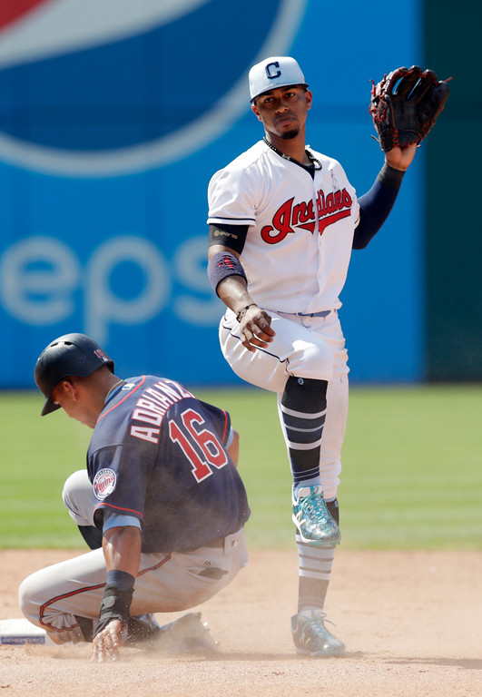 . Cleveland Indians\' Francisco Lindor, right, looks toward first base after getting Minnesota Twins\' Ehire Adrianza, left, out at second base in the ninth inning of a baseball game, Sunday, June 17, 2018, in Cleveland. Joe Mauer was out at first base for the double play. (AP Photo/Tony Dejak)