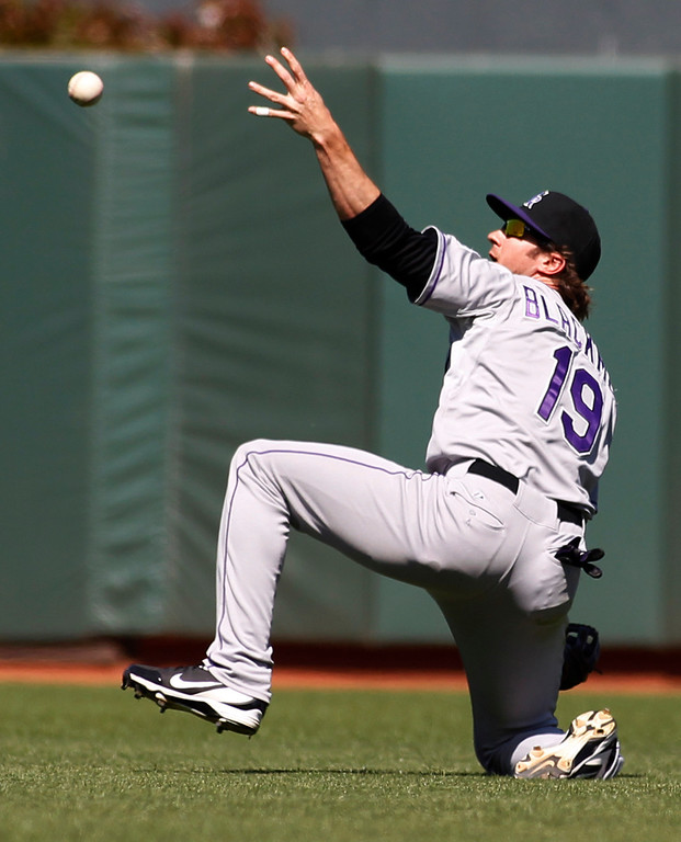 . Colorado Rockies\' Charlie Blackmon grabs for a ball hit by San Francisco Giants\' Hunter Pence during the sixth inning of a baseball game on Sunday, May 26, 2013 in San Francisco. Pence reached second base. (AP Photo/George Nikitin)