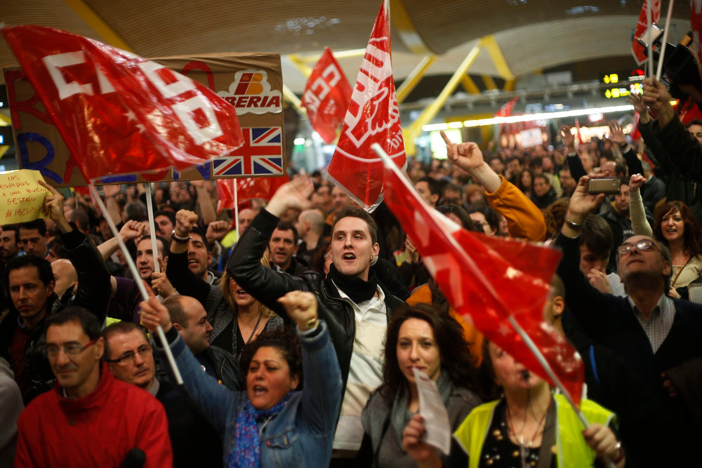 . Iberia airline workers shout slogans during a protest at Madrid\'s Barajas airport February 18, 2013. Striking union workers clashed with police at the airport on Monday on the first day of a week-long strike over more than 3,800 pending job cuts at Spain\'s flagship airline Iberia. REUTERS/Susana Vera