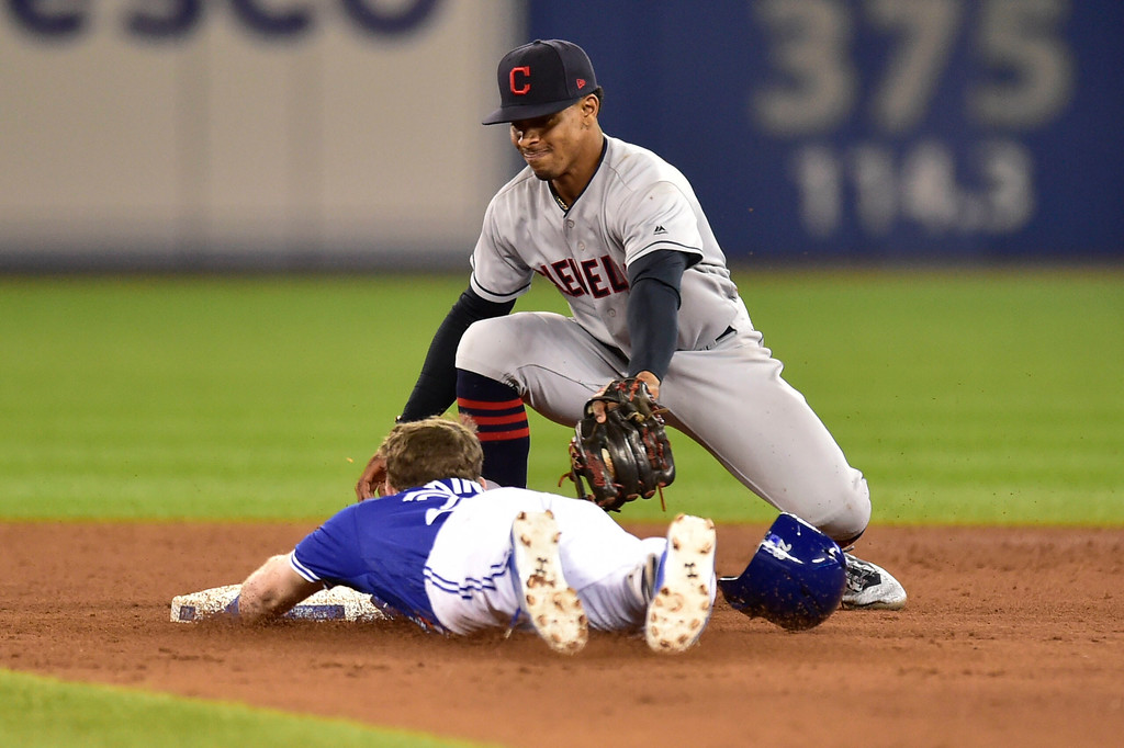 . Toronto Blue Jays Billy McKinney slides into second base with a double as Cleveland Indians shortstop Francisco Lindor (12) applies the tag during eighth inning baseball action in Toronto, Sunday, Sept. 9, 2018. (Frank Gunn/The Canadian Press via AP)