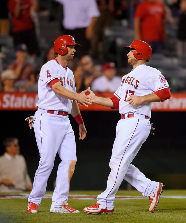 . Los Angeles Angels\' Kirk Nieuwenhuis, left, and Chris Iannetta congratulate each other after scoring on a single by Johnny Giavotella during the eighth inning of a baseball game against the Detroit Tigers, Sunday, May 31, 2015, in Anaheim, Calif. (AP Photo/Mark J. Terrill)