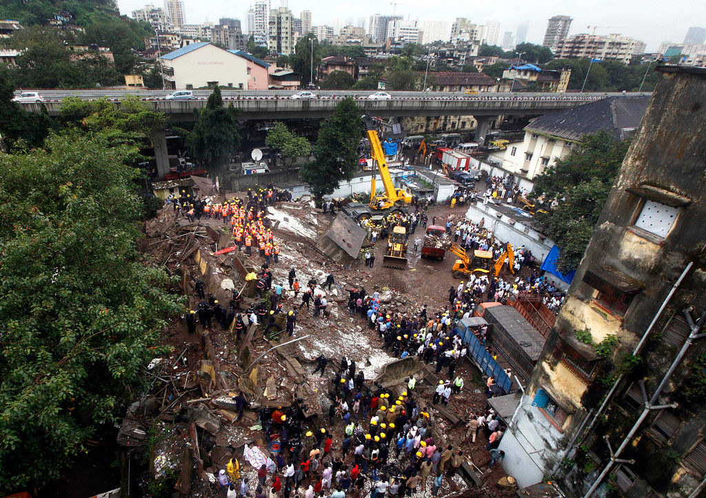 . Indian Fire officials look for survivors from debris of a collapsed building in Mumbai, India, Friday, Sept. 27, 2013. (AP Photo/Rajanish Kakade)