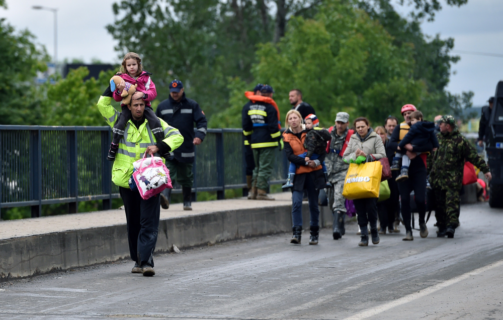 Description of . People evacuated from their flooded houses cross a bridge in the town of Obrenovac, 40 kilometers west of Belgrade, on May 17, 2014. Deadly floods across Bosnia and Serbia have claimed at least 14 lives and led to the evacuation of 15,000 people after the Balkans suffered its heaviest rainfall in a century, officials said today. In Serbia,