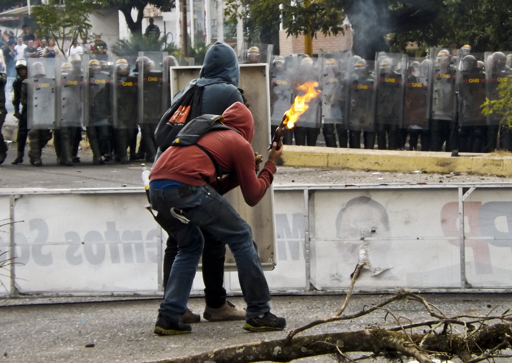 . Activists prepare to throw a molotov cocktail at National Guard troopers in riot gear during a protest in San Cristobal, capital of the western border state of Tachira, Venezuela, on February 21, 2014. At least 25 people were injured in late Saturday clashes with security forces that were some of the most serious to date. Venezuela\'s president on Sunday called for crisis talks in an attempt to defuse weeks of often deadly anti-government protests that have brought the biggest challenge yet to his regime. (ORLANDO PARADA/AFP/Getty Images)