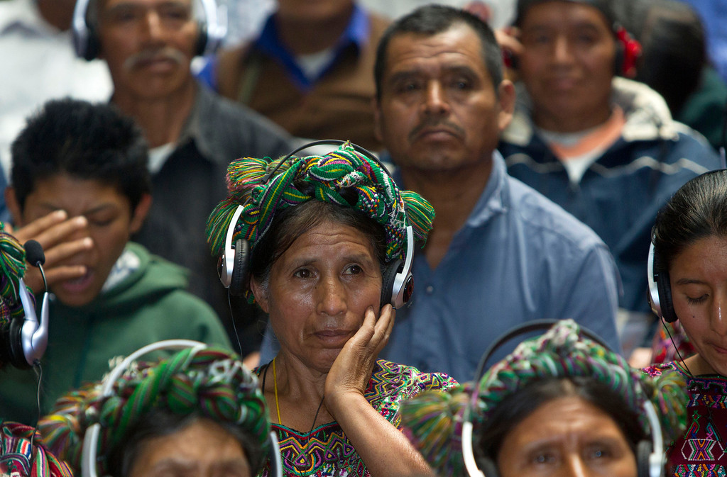 """. An Ixil Indian woman, the relative of a civil war victim, uses earphones to hear translations between Spanish and the Ixil language during the genocide trial of former dictator Jose Efrain Rios Montt in Guatemala City, Thursday, May 9, 2013.  The 86-year-old ex-general says he never ordered attacks against \""""a race,\""""denying he ordered the extermination of Ixil Mayas. Prosecutors say that while in power, Rios Montt was aware of, and thus responsible for, the slaughter of at least 1,771 Ixil Mayas in the towns of San Juan Cotzal, San Gaspar Chajul and Santa Maria Nebaj in Guatemala\'s western highlands. (AP Photo/Moises Castillo)"""